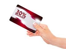 Dé sostener la tarjeta roja del descuento aislada sobre blanco Imágenes de archivo libres de regalías