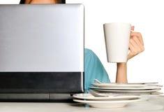 Dé sostener la taza detrás del ordenador portátil y de la pila de placas sucias en el escritorio Fotografía de archivo