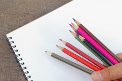 Dé sostener los lápices del color con el cuaderno de notas blanco llano en la tabla en el fondo Foto de archivo