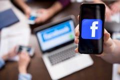 Dé sostener smartphone con el icono del logotipo del facebook en la pantalla Foto de archivo libre de regalías