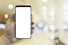 Dé sostener smartphone con el interior de la falta de definición en alameda de compras Foto de archivo