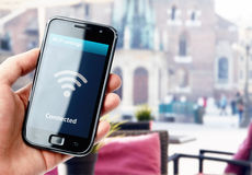 Dé sostener smartphone con la conexión de Wi-Fi en café Imagenes de archivo
