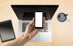 Dé sostener smartphone con la pantalla en blanco sobre el escritorio foto de archivo libre de regalías