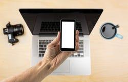 Dé sostener smartphone con la pantalla en blanco sobre el escritorio fotos de archivo libres de regalías
