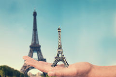 Dé sostener un juguete del recuerdo de la torre Eiffel, torre Eiffel real en el fondo Imagen de archivo