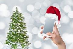 Dé sostener un smartphone con el sombrero de Papá Noel, el árbol de navidad y el fondo del bokeh Fotografía de archivo libre de regalías