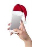 Dé sostener un smartphone con un sombrero de la Navidad aislado en blanco Fotos de archivo
