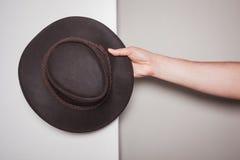 Dé sostener un sombrero de vaquero contra fondo coloreado dual imagenes de archivo