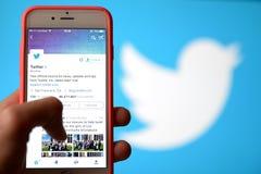 Dé sostener un teléfono móvil y usar la red social Twitter Imágenes de archivo libres de regalías