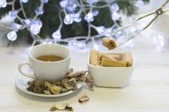 Dé sostener una galleta con pinzas y una taza de té Fotografía de archivo libre de regalías