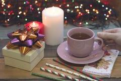 Dé sostener una taza de té, de una caja de regalo y de velas ardientes Imagenes de archivo