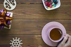 Dé sostener una taza de té rosado, decoraciones de la Navidad y los caramelos imagenes de archivo