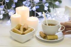 Dé sostener una taza de té, velas ardientes, galletas en un cuenco Imagen de archivo