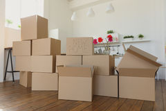 Déballant des boîtes dans de nouvelles choses à la maison et mettantes loin dans la cuisine, grandes boîtes en carton dans la nou Photographie stock libre de droits