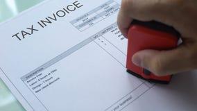 Débito da fatura do imposto, mão do trabalhador que carimba o selo no documento comercial, negócio filme