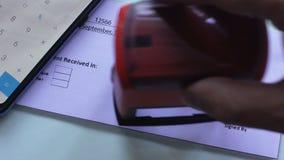 Débito do documento do recibo do aluguel, mão que carimba o selo no papel oficial, falência filme