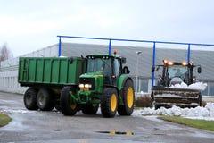 Déblaiement de neige d'hiver avec des tracteurs de John Deere et de Valtra Photos stock