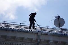Déblaiement de neige du toit de l'entretien de Chambre et du soin du toit pendant l'hiver La Russie Berezniki le 2 avril 2018 photos stock