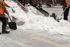 Déblaiement de neige sur les rues Plan rapproché d'un chasse-neige et des travailleurs de route avec des pelles Les gens et les v photographie stock