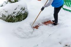 Déblayement de la femme de neige tandis que Photographie stock libre de droits
