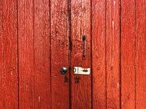 Débloqué mais fermé ; porte en bois rouge Photos stock