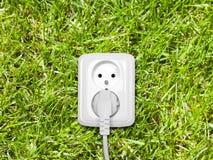 Débouché électrique sur l'herbe verte Photos libres de droits