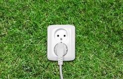Débouché électrique sur l'herbe verte Photographie stock