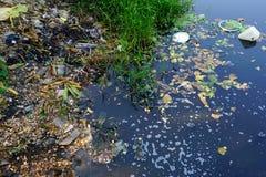 Débris en plastique jetés polluant une voie d'eau Images libres de droits