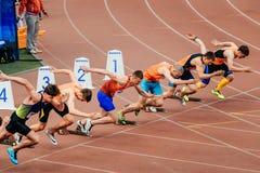 début d'hommes de coureurs de sprinters courant 100 mètres Image stock