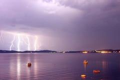 Début d'une tempête en mer avec des foudres en ciel pourpre Photos stock