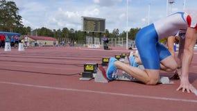 Début et course de bloc commençant de sprinters d'athlètes d'hommes banque de vidéos