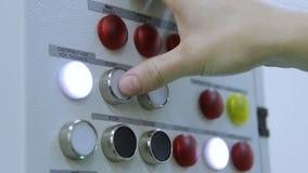 Début humain de pressing de main et boutons ouverts sur le panneau de commande à l'usine clips vidéos