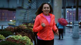 Débuts sportifs de femme de jeune métis fonctionnant le long du remblai de parc de ville le soir, tir de mouvement lent clips vidéos