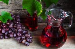 Décanteur de vigne et un verre de jus de raisins Images libres de droits