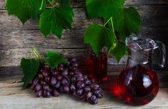 Décanteur de vigne et un verre de jus de raisins Photographie stock libre de droits