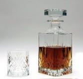 Décanteur de whiskey et à moitié plein en verre avec l'esprit Photographie stock libre de droits