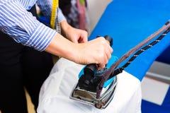 Décapant dans la veste repassante de boutique de blanchisserie photo stock