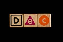Décembre sur cubique en bois sur le fond noir Photo libre de droits