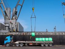 Décharge des produits en acier par la grue de bateau image stock