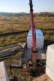 déchargement des blocs par la grue d'automobile sur le chantier de construction images stock