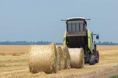 Décharges de tracteur et de presse ronde Straw Bales images libres de droits