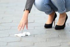 Déchets de cueillette de femme du trottoir sur la rue photos stock