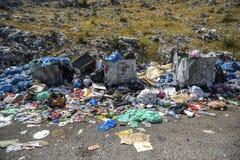 Déchets se renversant hors des déchets près d'un pré vert image libre de droits