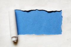 Déchirement d'un trou de papier de cadre avec le fond bleu Images libres de droits