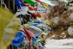 Déchirez les drapeaux tibétains colorés de prière ondulant et enveloppés avec le pont au-dessus de la rivière congelée à la vallé Photos libres de droits