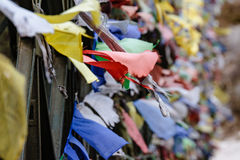 Déchirez les drapeaux tibétains colorés de prière ondulant et enveloppés avec le pont au-dessus de la rivière congelée à la vallé Photographie stock libre de droits