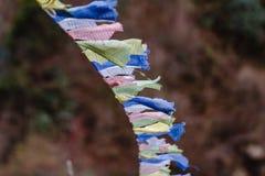 Déchirez les drapeaux tibétains colorés de prière ondulant et enveloppés avec le pont au-dessus de la rivière congelée à la vallé Image stock
