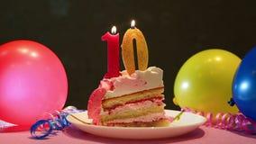 Décima torta de cumpleaños feliz y número rosado diez velas con los globos almacen de video