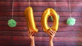 Décimo cumpleaños feliz, balones de aire de oro con el número diez, aniversario almacen de video