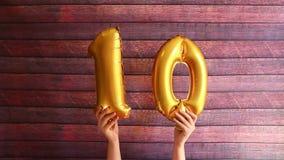 Décimo cumpleaños feliz, balones de aire de oro con el número diez, aniversario metrajes